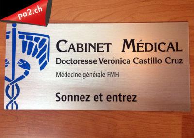 Plaque signalétique de porte d'entrée du cabinet médical de Saillon en alu brossé avec un logo bleu et des inscriptions noires en vinyle découpé. Centre de secour incendie écrit en letres blanche de deux centimètre d'épaisseur. Réalisé par Pa2.ch