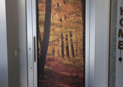 Porte d'entrée recouverte d'un autocollant imitation tapisserie représentant un bois en automne. Réalisé par Pa2.ch