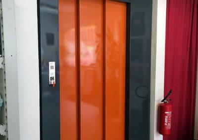 Porte d'ascenseur avec une peinture ancienne en cours de recouvrement de vinyle, deux couleurs. gris et orange. Réalisé par Pa2.ch