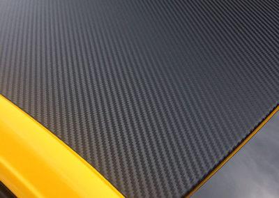 Vue d'un toît de voiture jaune recouvert de vinyle à effet carbone noir. Portière intérieur de voiture recouverte de vinyle à effet carbone noir. Réalisé par Pa2.ch